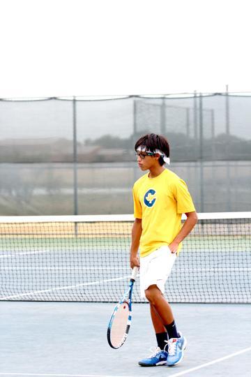 Varsity player Daniel Barrera prepares to serve.
